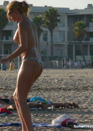 Женщина предпочитает загорать в купальнике без верха и не замечает, как ее снимают на камеру