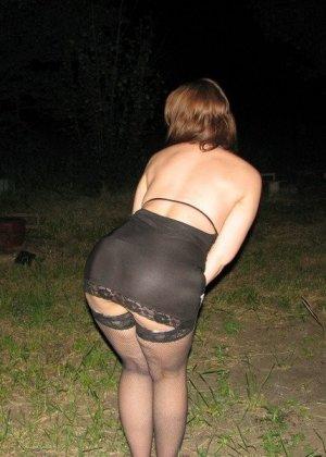 Женщина показывает свое тело в эротичном прикиде посреди ночи прямо на природе – она скрывает только лицо