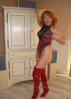 Рыжая женщина в красных ботфортах