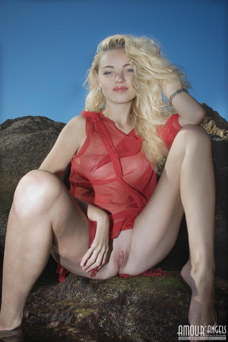 Худая блондинка в прозрачной красной накидке показывает бритую киску на пляже