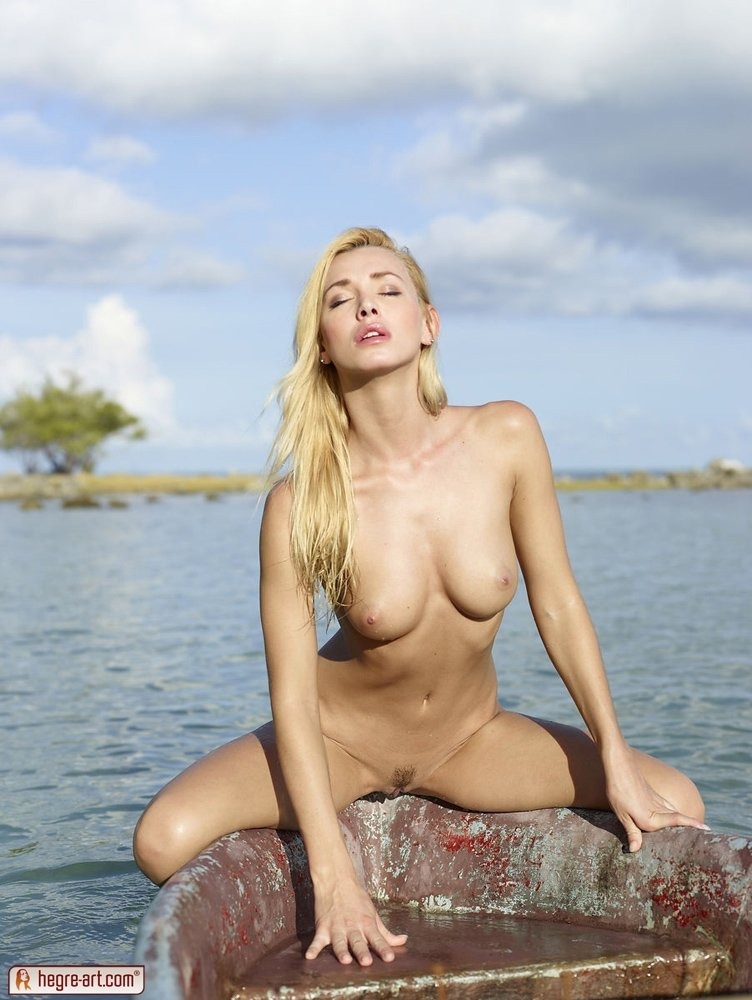 Блондинка с красивой грудью катается голая в старой лодке