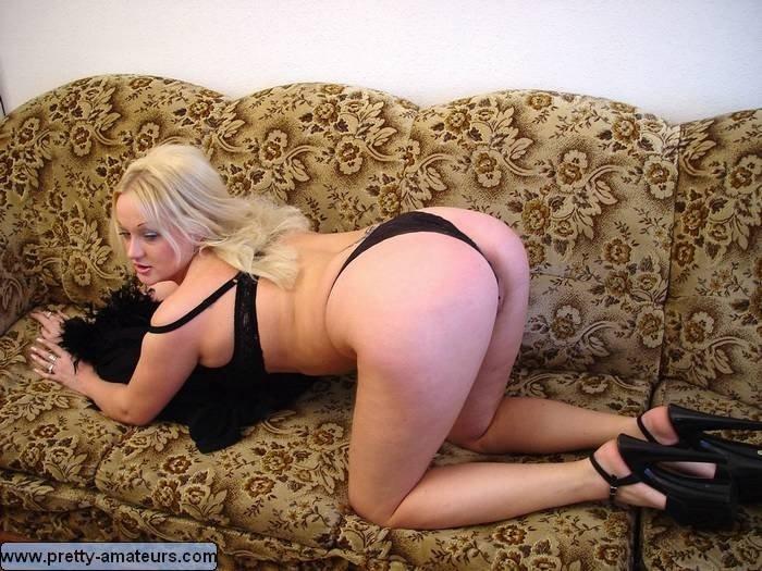Светловолосая пухлая дамочка позирует на диване
