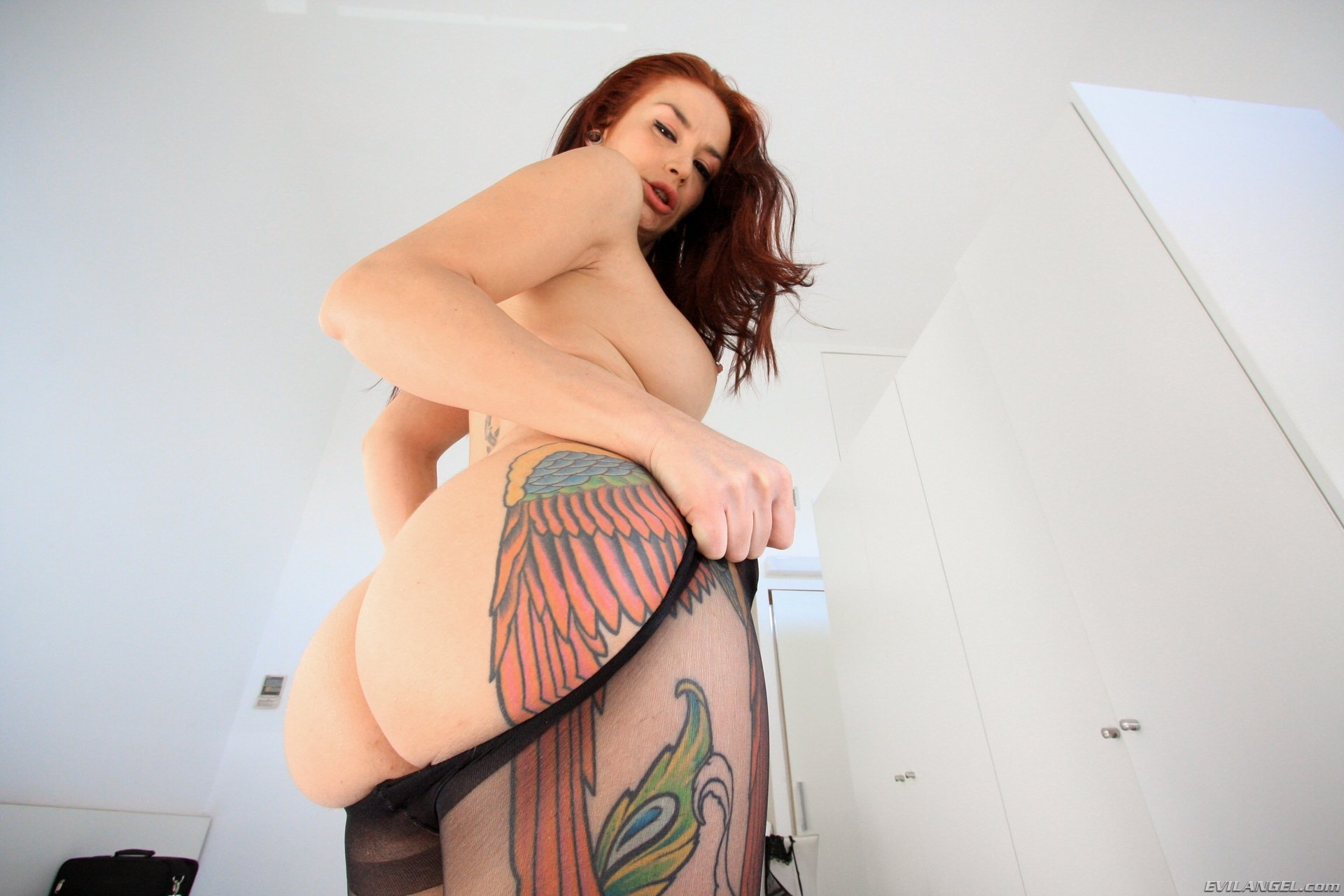 Рыжая длинноволосая проблядь с большой татухой на бедре