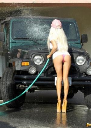 Блондинка Кортни моет машину в розовом купальнике