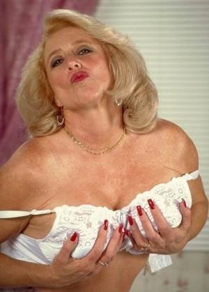 Голая пожилая блондинка гладит свою пизду на кровати