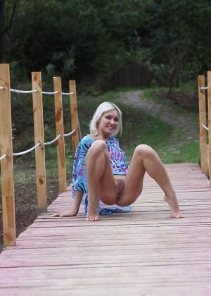 Стройная Настя сексуально позирует на мосту, задирая легкое платье, под которым нет ничего