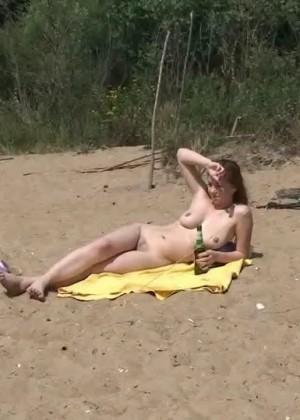 Компания молодых людей отдыхает на пляже в голом виде