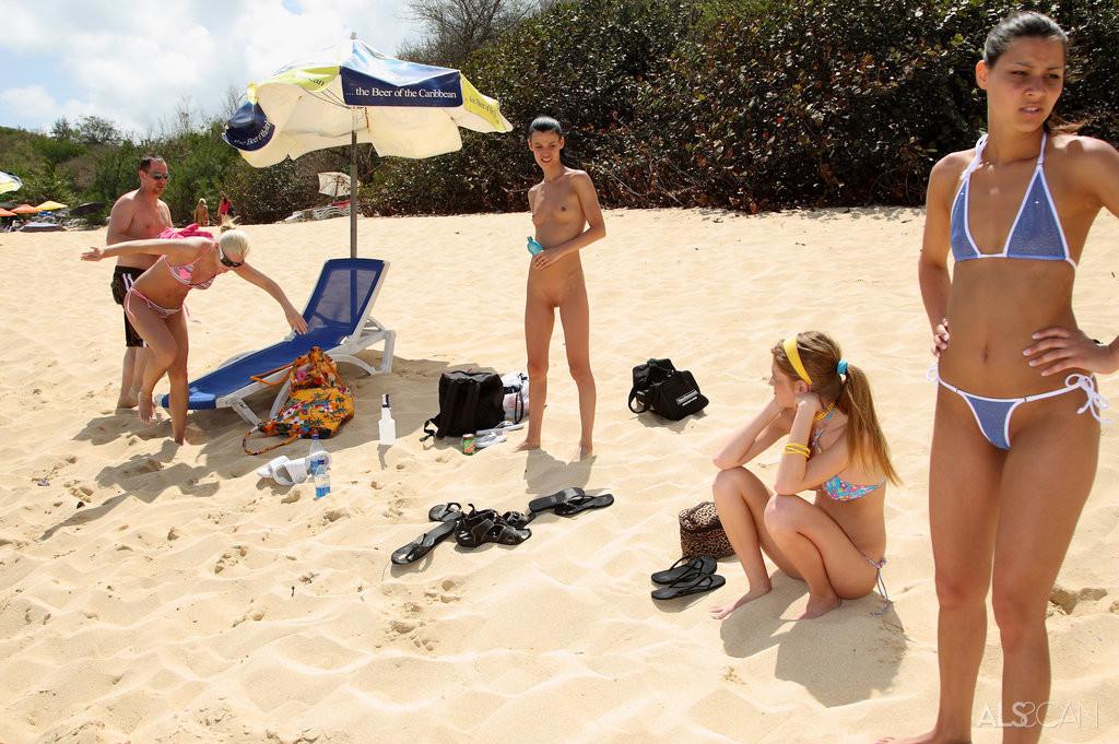 Две красивые девушки на пляже целуют свои бритые влагалища