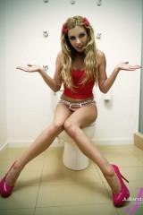 Длинноногая блондинка Лекси Белл сидит на унитазе