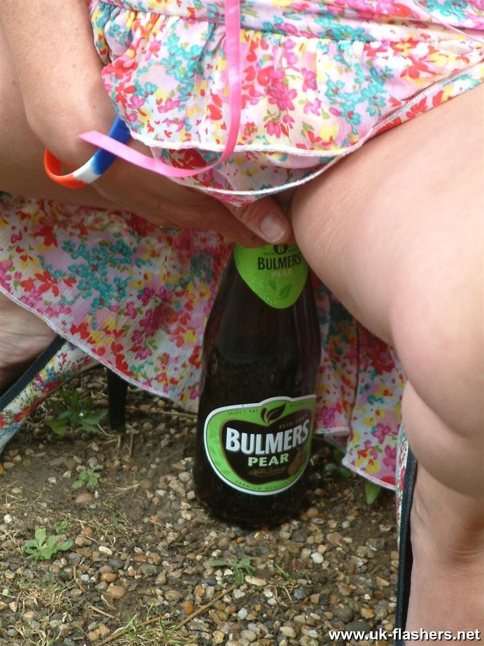Женщина сначала просто приподнимает платье, чтоб показать пизду, а затем насаживается на стеклянную бутылку