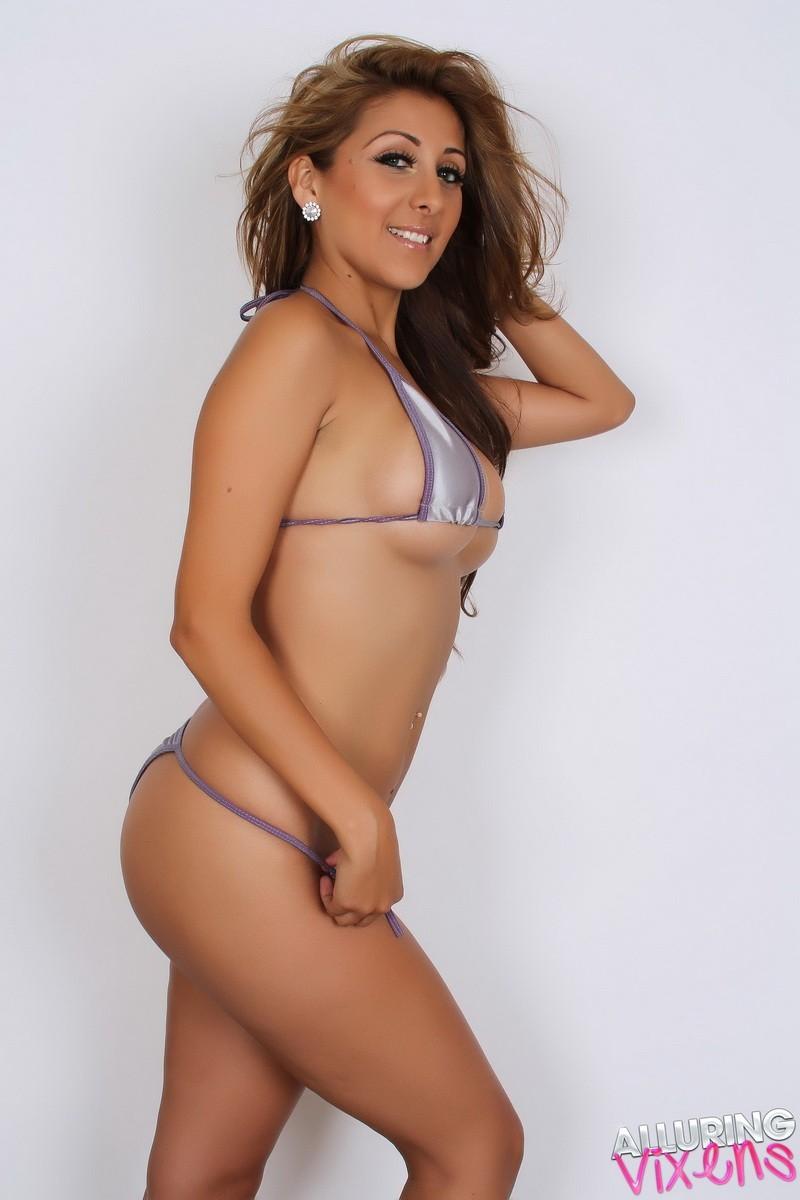 Горячая модель с экзотической внешностью показывает свою красивую фигуру под крохотным бикини