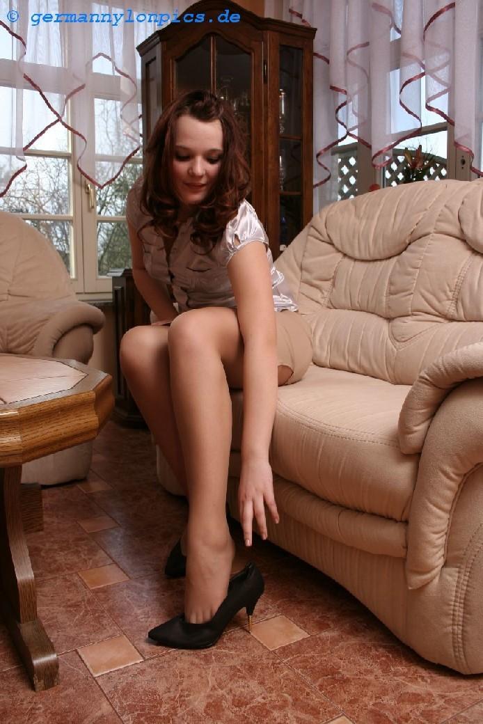 Девушка снимает туфли после тяжелого дня и показывает свои ножки в капроновых колготках