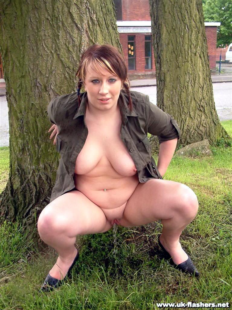Телка не скрываясь, мочится у дерева, широко разведя ноги, чтобы получше было видно все подробности