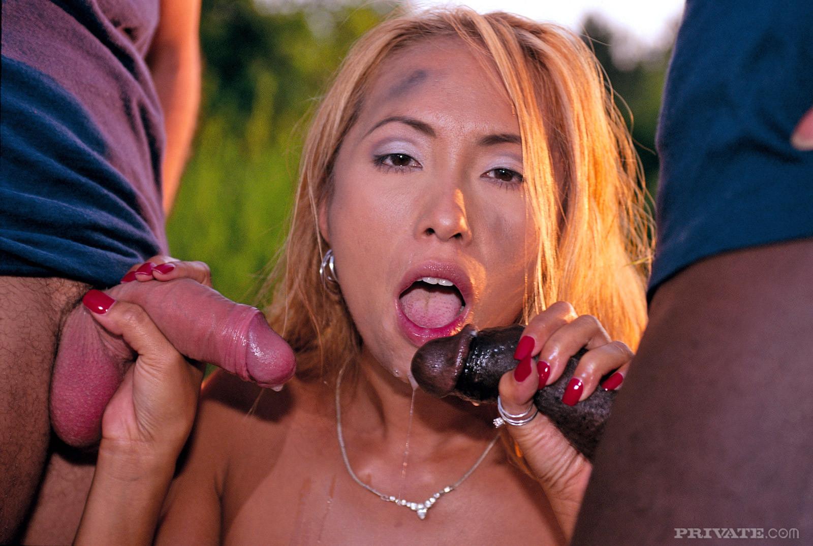 Рыжая азиатская шлюшка сосет белый и черный член, а они ее трахают прямо на грязной земле