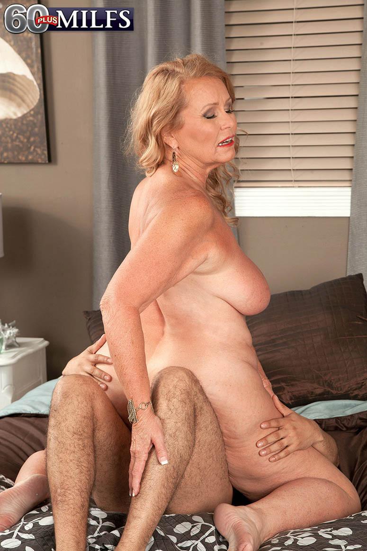Зрелая блонда соблазняет парня своими большими титьками и позволяет ему трахать ее, как только ему захочется