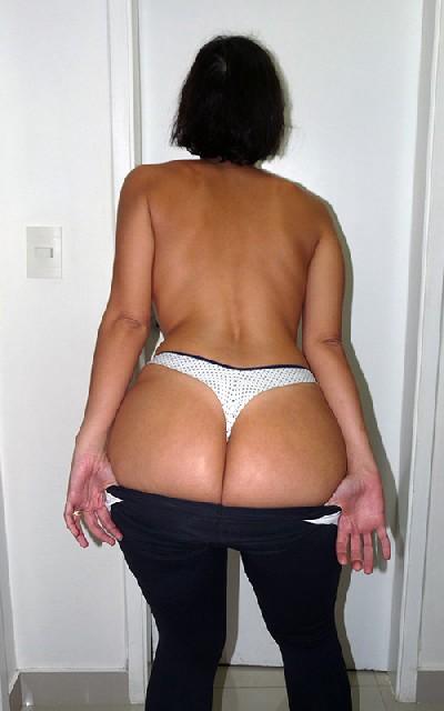 Женщина встает спиной к камере и показывает свою большую задницу в одежде, а затем в трусах