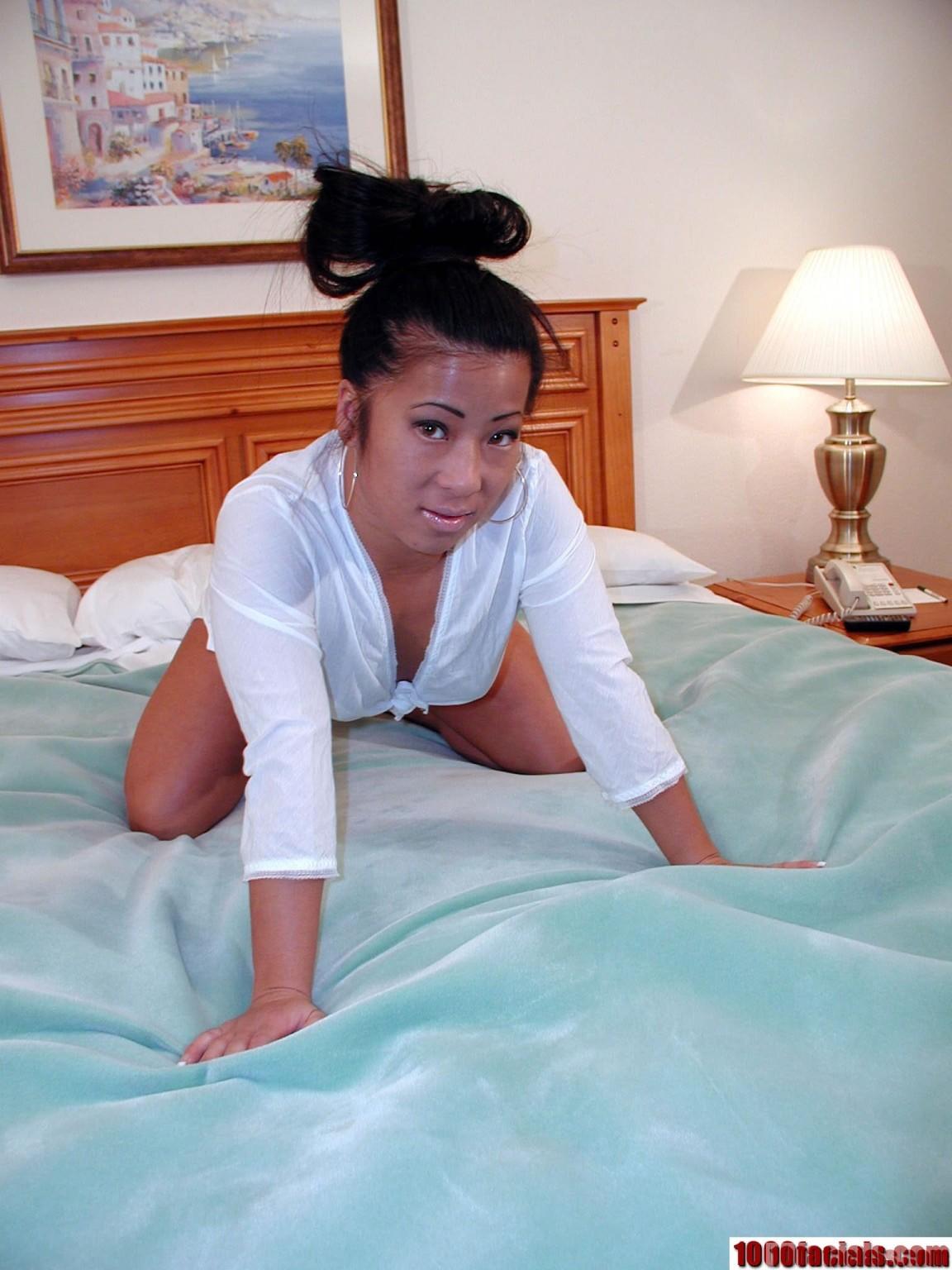 Азиаточка в белом раздевается на кровати и берет за щеку у своего парня