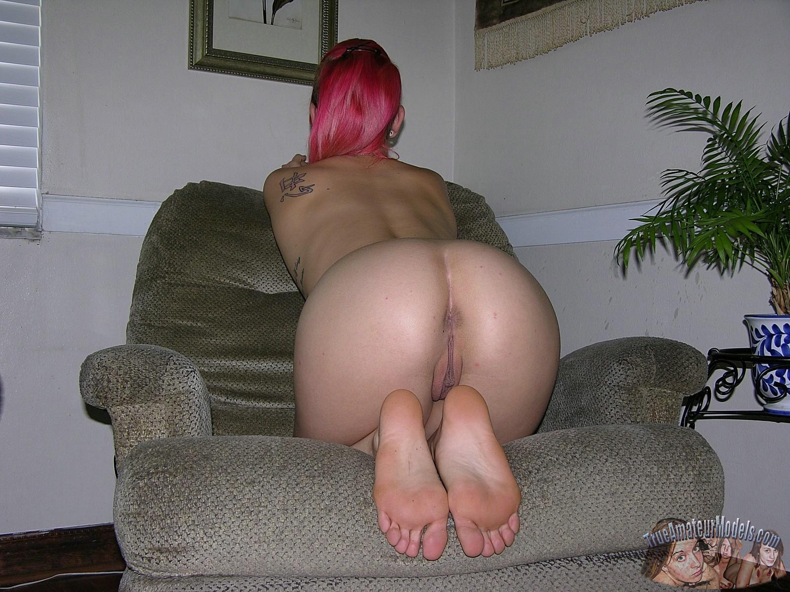 Девушка с красными волосами позирует перед камерой в голом виде