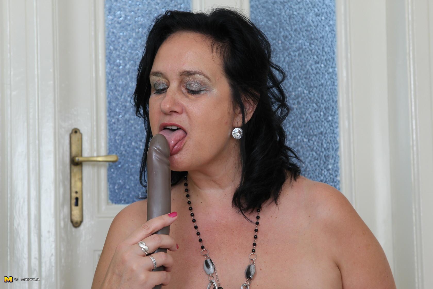 Зрелая женщина показывает свое пышное тело, а затем принимается облизывать искусственный фаллос