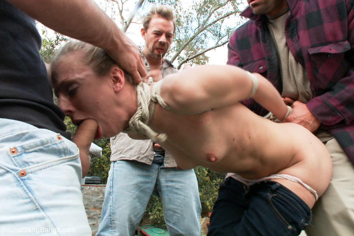 Обмотав телку вокруг горла веревкой мужики суют ей в рот члены