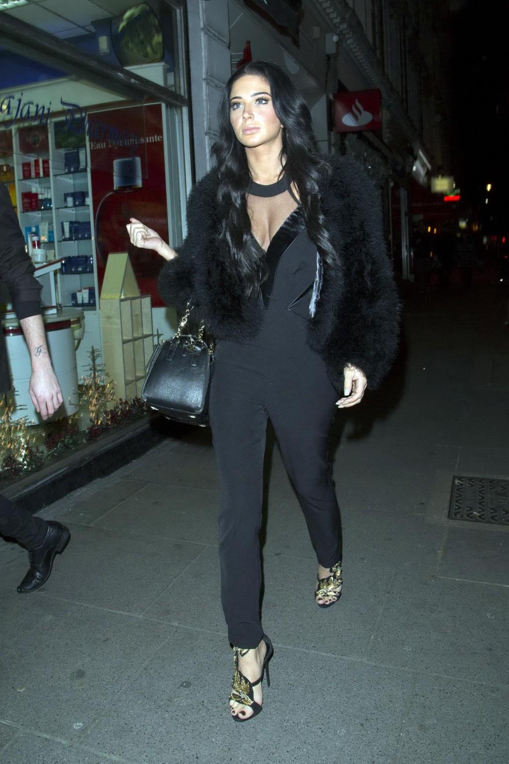 Брюнетка с шикарными длинными волосами прогуливается по вечернему городу