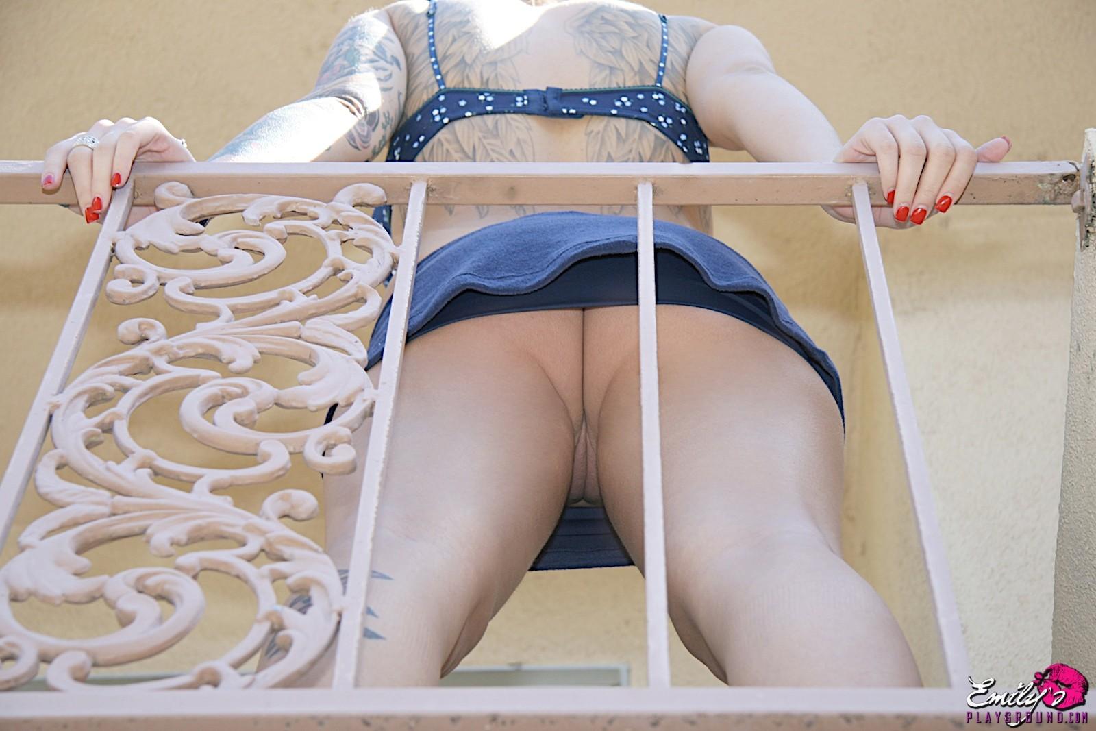 Девушка в короткой юбке и без трусиков стоит у перил