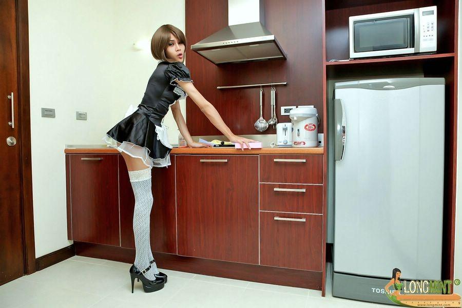 Горячая домработница в белых чулках позирует перед камерой на кухне