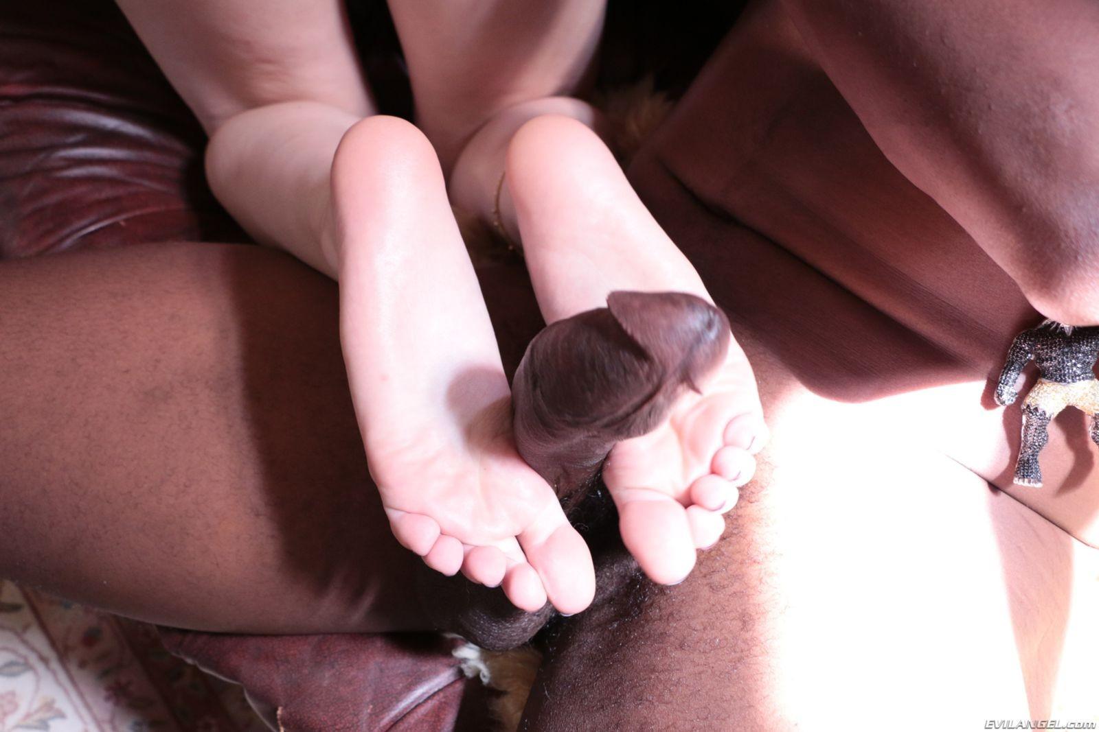 Брюнетка мастурбирует негру хуй своими тонкими нежными ногами