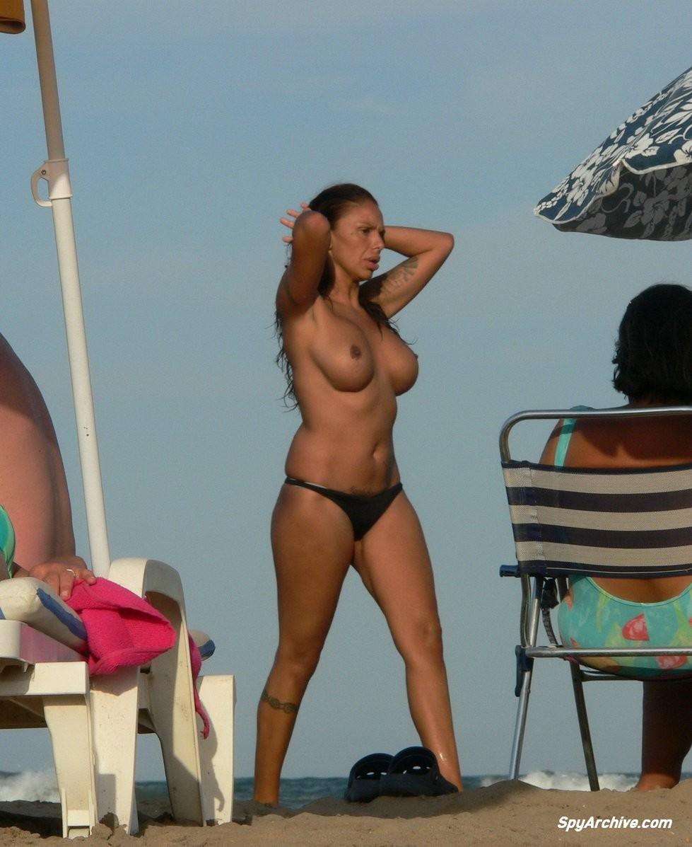 Горячая пышная дамочка в татуировках загорает на пляже и совсем не стесняется обнажаться