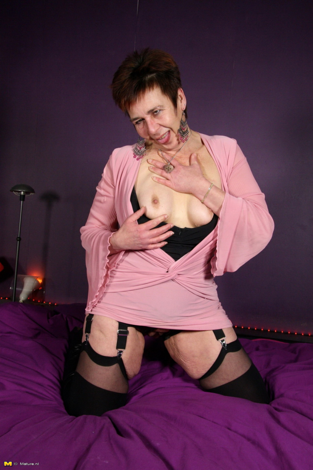 Зрелая женщина в эротичном костюме показывает себя всю, принимая самые откровенные позы