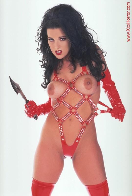 Роковая брюнетка в красном латексе позирует перед фотографом, обнажая самые соблазнительные части тела