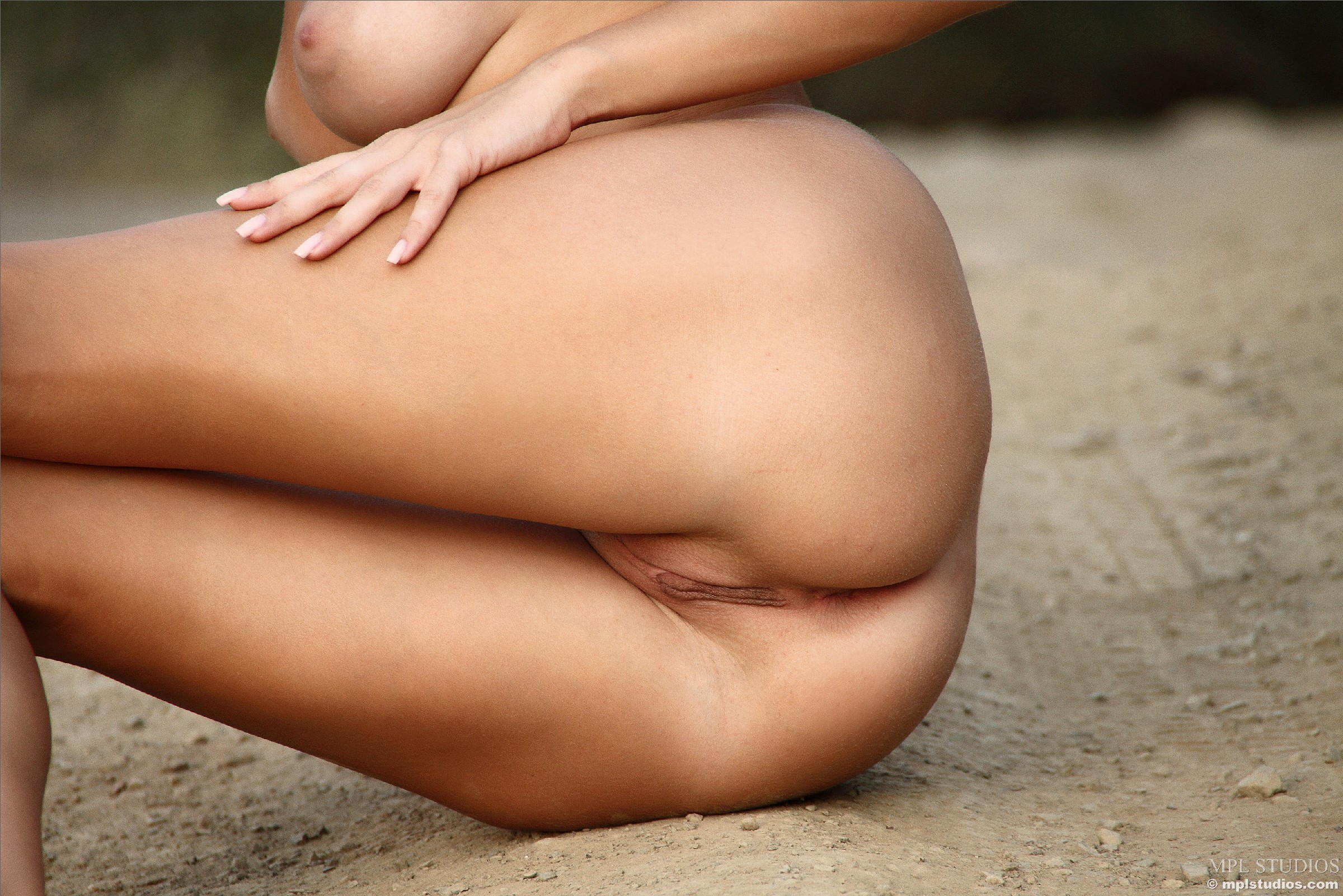 Блондинка на природе позирует перед фотоапаратом в сексуальных позах