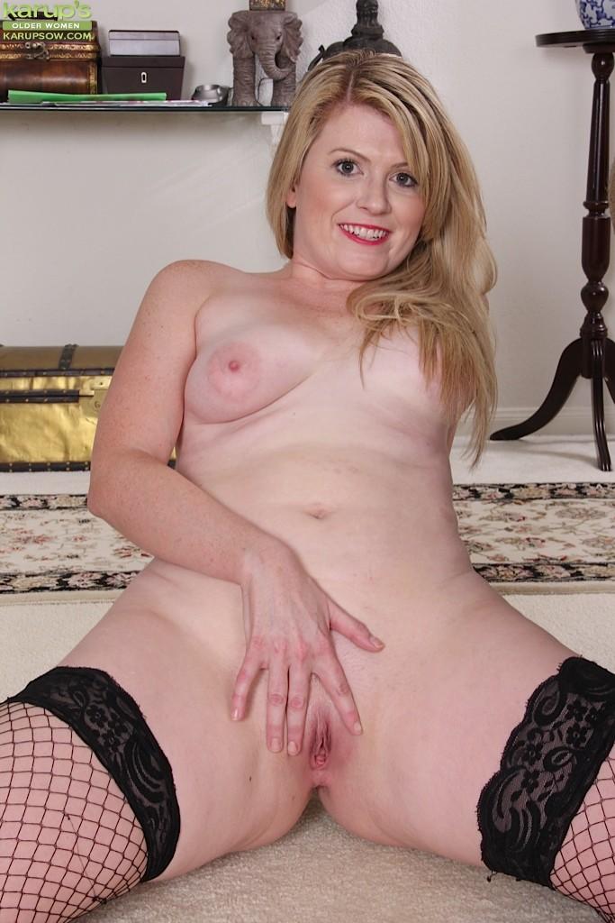 Девушка в черных чулках мастурбирует себе промежность на  полу