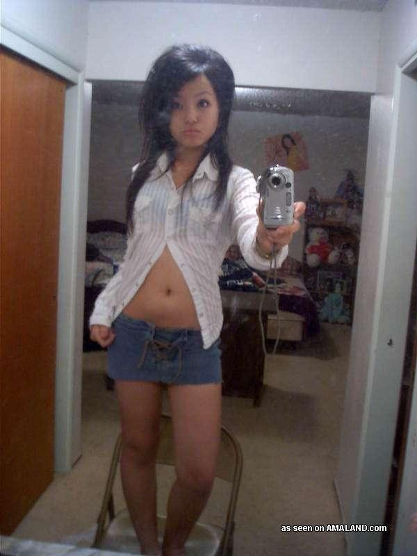 Сексуальная азиатка симпатичной внешности делает красивые фото на телефон