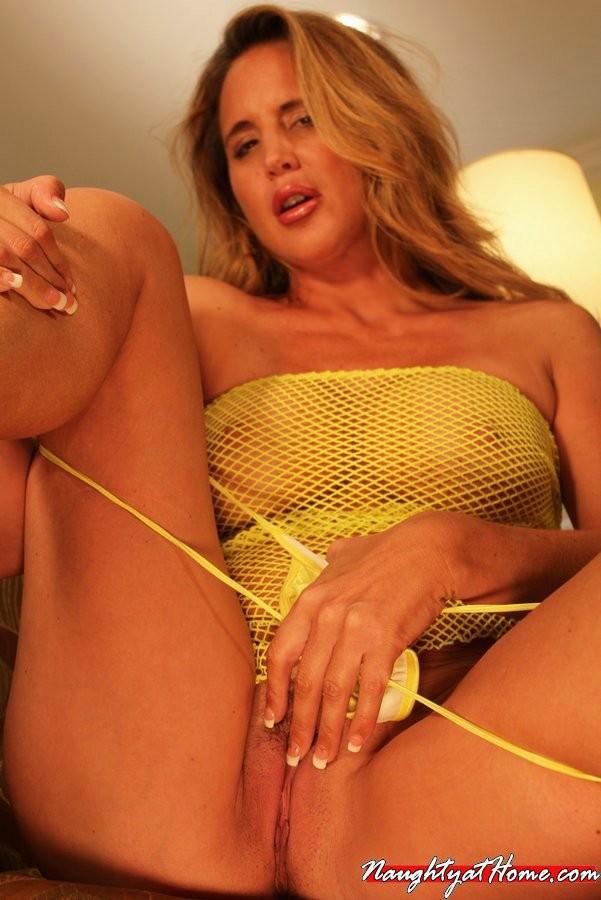 Опытная дамочка показывает свое сексуальное тело, медленно снимая желтую сетчатую маечку