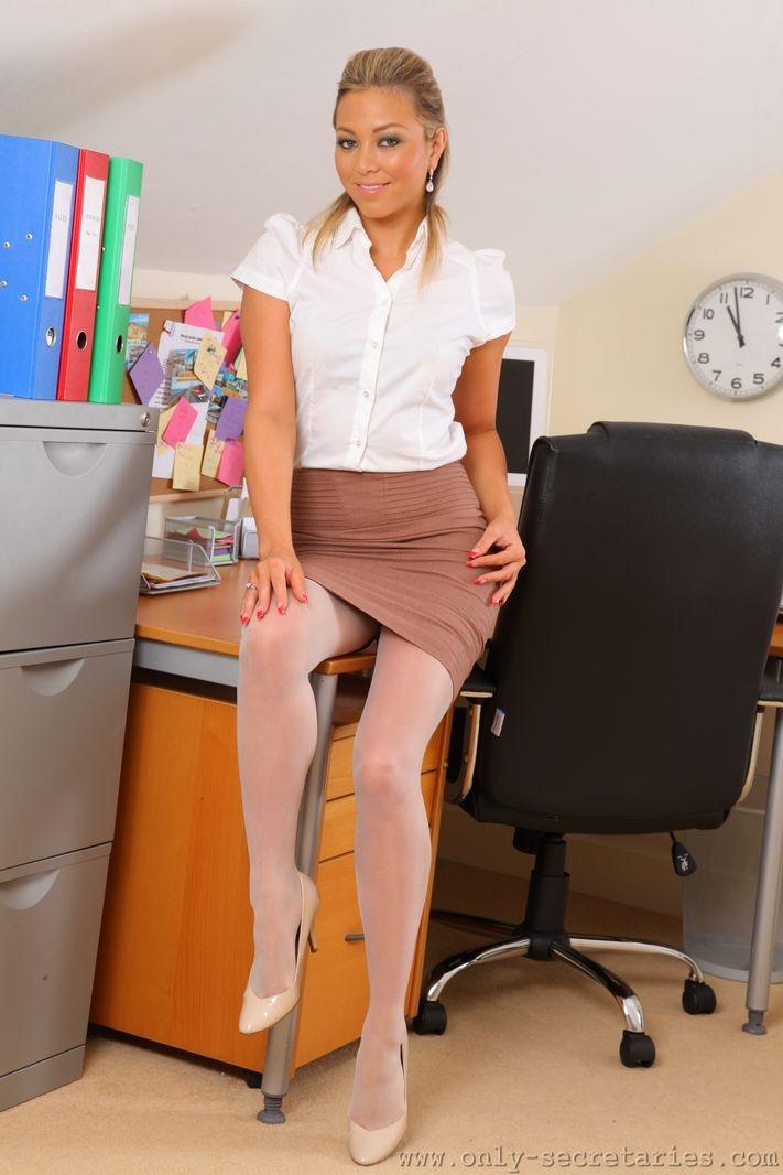 Привлекательная секретарша со светлыми волосами снимает колготки и показывает свои белоснежные трусики