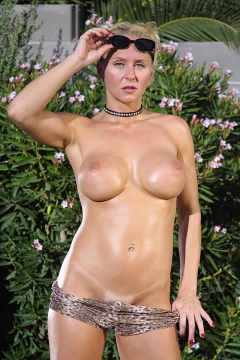 На заднем дворе блондинка с большими силиконовыми сиськами разделась догола