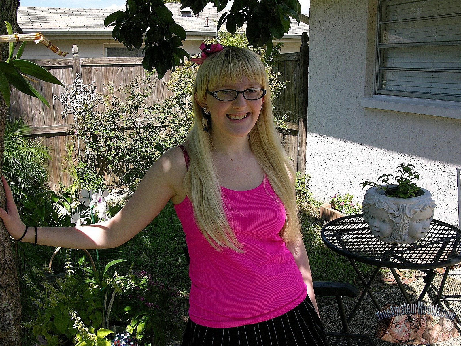 В домашних условиях некрасивая блондинка в очках показывает обе дырочки