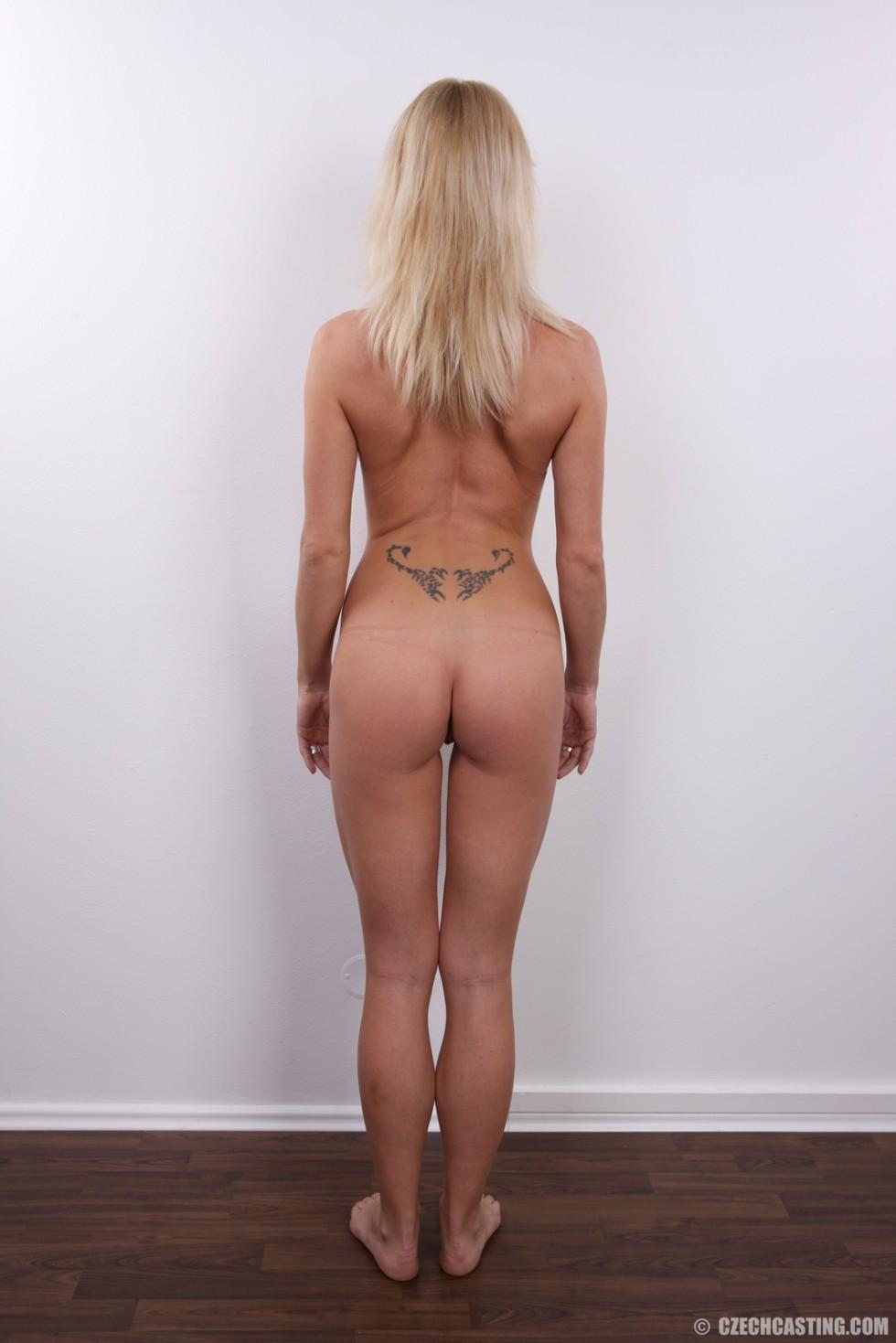 Девушка позирует перед камерой в обнаженном виде у стула