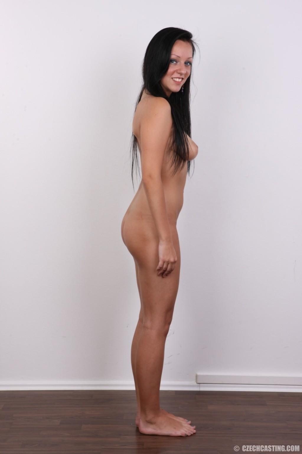 Девушка с весящими дойками улыбается голая на камеру в офисе