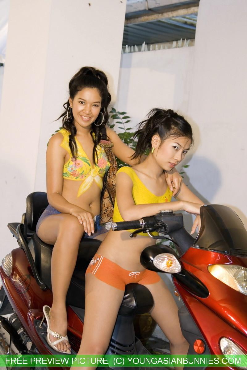 Молодые девушки обливают себя водой в майке без лифчика у мопеда