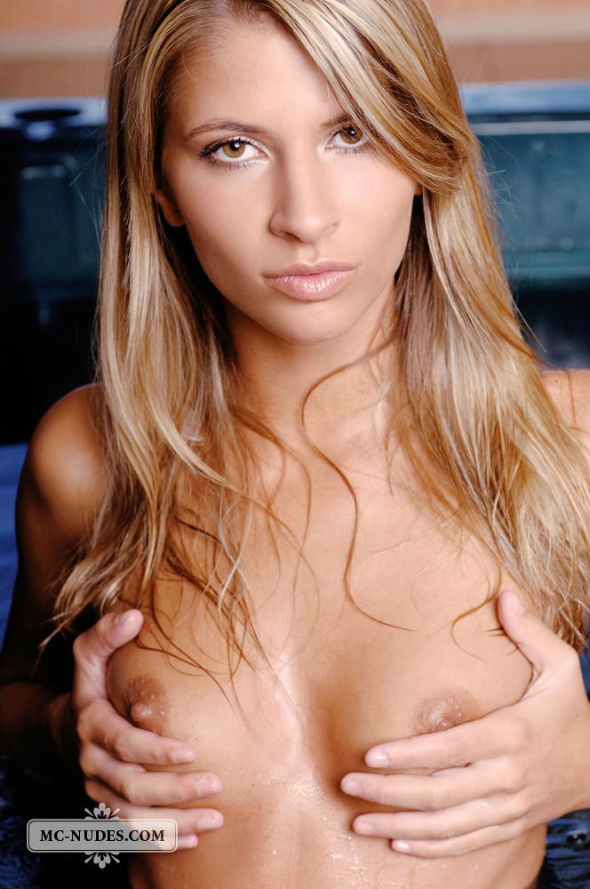 Сексуальная блондинка средних лет очень красиво и эротично позирует сначала на полу, а потом в бассейне
