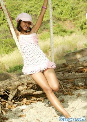 Девушка-азиатка качается на качелях и показывает свое хрупкое тело, раскрывая некоторые интимные части - фото 8