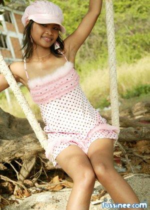 Девушка-азиатка качается на качелях и показывает свое хрупкое тело, раскрывая некоторые интимные части - фото 5
