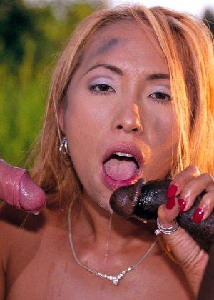 Рыжая азиатская шлюшка сосет белый и черный член, а они ее трахают прямо на грязной земле - фото 12