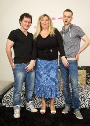 Зрелая женщина очень радуется вниманию двух молодых людей и показывает им свою огромную грудь - фото 2