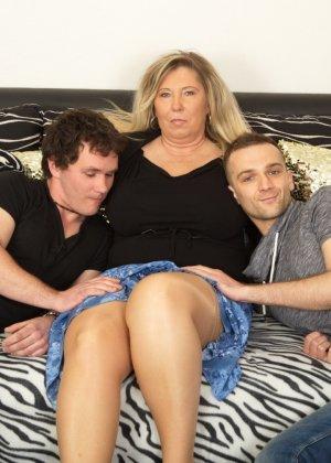 Зрелая женщина очень радуется вниманию двух молодых людей и показывает им свою огромную грудь - фото 5