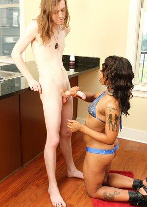 Настоящая темнокожая чертовка дрочит член белому неопытному парню, стоя на коленках в кухне - фото 7