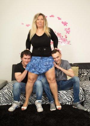 Зрелая женщина очень радуется вниманию двух молодых людей и показывает им свою огромную грудь - фото 3