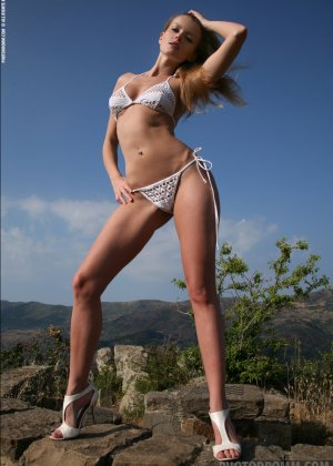 Красивая телочка обнажила свое изысканное тело на природе у скалы - фото 1